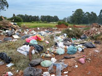 """A CÉU ABERTO — Sacos de lixo recolhidos na área urbana são jogados no """"lixão"""" e permanecem dias sem cobertura, aumentando o mau cheiro"""