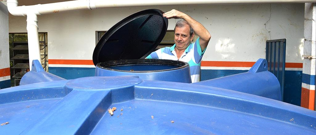 "O coordenador Sérgio Pereira Dias mostra tampa da cisterna que já funciona na escola ""Zilda Comegno Monti"""